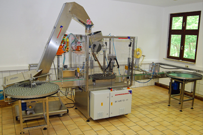 Linear semi-automatic filling, capping and labelling machine from Küppersbusch.