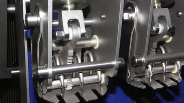 Bearing arrangement of the sliced goods holder in depositing fork design. Drive occurs via pneumatic cylinders for realisation of the swivelling motion with iglidur® J plain bearings.